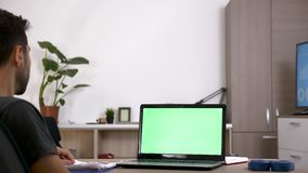 Man at his desk in front of computer with green screen