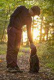 Man and his dog enjoying nature. As he stands bending down to pet it in a glade in the woods backlit by the warm glow of the early morning sun Stock Images