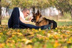 Man And His Dog German Shepherd. Man Llying Down Outdoors With His Pet Dog German Shepherd stock photo
