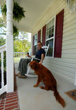 Man and his dog at home. A relaxed happy man at home sitting in a rocking chair on a porch with his pet dog and cup of coffee, early retirement Stock Photo