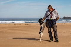 A man and his dog look at each other on the beach.