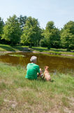Man with his dog near the water Royalty Free Stock Photography