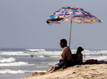 Man and his dog relaxing at the beach. Under an umbrella Royalty Free Stock Photography