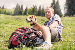 Man with his dog rest on the mountain hill Royalty Free Stock Photography