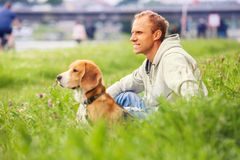 Man with his dog sitting in green grass Royalty Free Stock Image