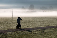 Man and his dog standing in a yard covered by fog Royalty Free Stock Images