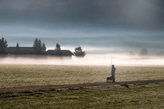 Man and his dog standing in a yard covered by fog Royalty Free Stock Photo