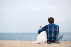 Man with his dog at the summer beach sitting back to camera Stock Photo