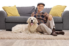 Man and his dog together on the floor Stock Images