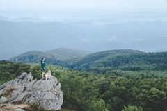 Man with his dog at the top of a mountain having a beautiful view Stock Photos