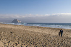 Man and his dog walking on empty beach with Morro Rock on Backgr Stock Photo