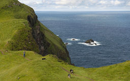Man and his dogs hiking on Mykines Royalty Free Stock Images