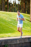 Man on his everyday jog. Full length of confident young man running along quayside Royalty Free Stock Photos