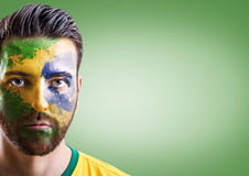 Man with his face painted with the Brazilian Flag on green background Stock Image