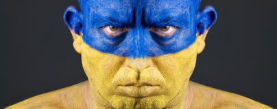 Man with his face painted with the flag of Ukraine Stock Photo