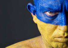 Man with his face painted with the flag of Ukraine Royalty Free Stock Photography