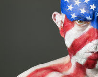 Man with his face painted with the flag of USA. The man is serious and photographic composition leaves only half of the face stock images