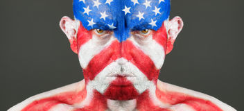 Man with his face painted with the flag of USA. The man is serious and photographic composition is panoramic royalty free stock image