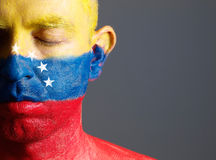 Man and his face painted with the flag of Venezuela and closed e Stock Image