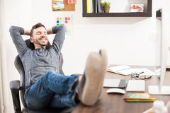 Man with his feet up the desk at an office Stock Images