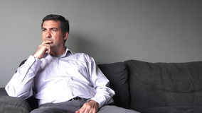 Man in his forties (40s) sitting on a sofa upset. Man middle age concept (slider motion) copy space stock video footage