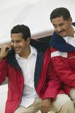 Man With His Friend On Call. Happy mature men with his friend using cell phone on the yacht Royalty Free Stock Image
