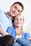 Man and his girl embrace each other on the sofa Royalty Free Stock Images