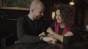 A man with his girlfriend in the cafe. Man pointing to his watch and said joke. A man with his girlfriend in the coffee shop. Man pointing to his watch and said stock video footage