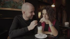 A man with his girlfriend in the coffee shop. Lovers drinking coffee from a cup. stock video