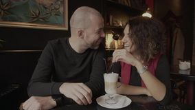 A man with his girlfriend in the coffee shop. Lovers drinking coffee from a cup. stock footage