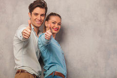 Man with his girlfriend posing in studio showing thumbs up. Young men with his girlfriend posing in studio background while showing thumbs up sign Royalty Free Stock Image