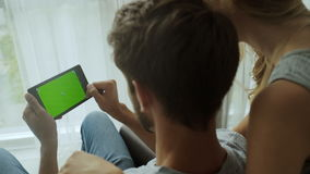 Man and his girlfriend using tablet. green screen Great for Mock-up, most popular gestures used. stock footage