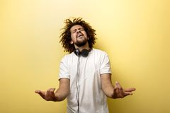 A man with his hair in a frizz and headphones on the neck is holding his hands in front of him and making a horn gesture stock photo