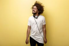 A man with his hair in a frizz and headphones on the neck is standing and looking cheerfully sideways wearing asymmetric. T-shirt over the yellow background stock image