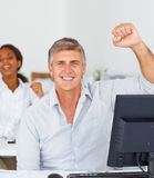 Man with his hand raised and his colleagues Stock Photography