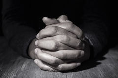 Man with his hands clasped. Closeup of the hands of a young caucasian man with his hands clasped on a wooden table Royalty Free Stock Image