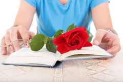 Man with his hands holding open book while rose and glasses are Stock Photo
