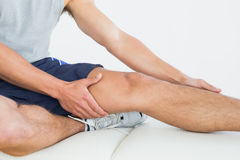 Man with his hands on a painful leg Stock Photography