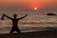 Man with his hands up on the dawn on the beach Stock Image