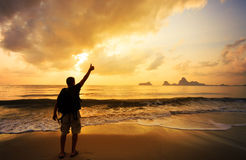 Man with his hands up on the dawn. On the beach Stock Image