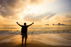 Man with his hands up on the dawn. On the beach Royalty Free Stock Photos