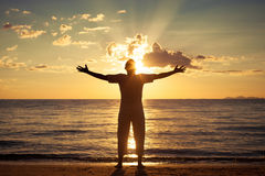 Man with his hands up at the sunset time stock photos