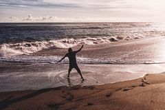 Man with his hands up at the sunset time on the beach royalty free stock photography