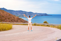 A man with his hands up at the top, admiring the sea Royalty Free Stock Image