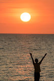 Man with his hands up watching the sun set Royalty Free Stock Images