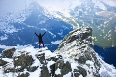 A man with his hands up, in which he keeps trekking poles. A man with his hands up, in which he keeps trekking poles, standing on a cliff, watches the Stock Images