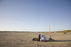 Bury your Head in the Sand. A man with his head in a hole, a literal picture of this saying stock images