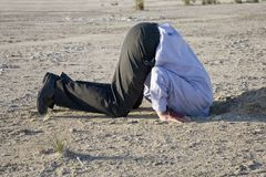 Bury your Head in the Sand. A man with his head in a hole, a literal picture of this saying stock photography