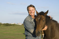 Man with his horse. Color portrait photo of a handsome smiling man petting his horse Royalty Free Stock Photography