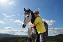 Man and his horse. Man hugging his grey lusitano horse Royalty Free Stock Images